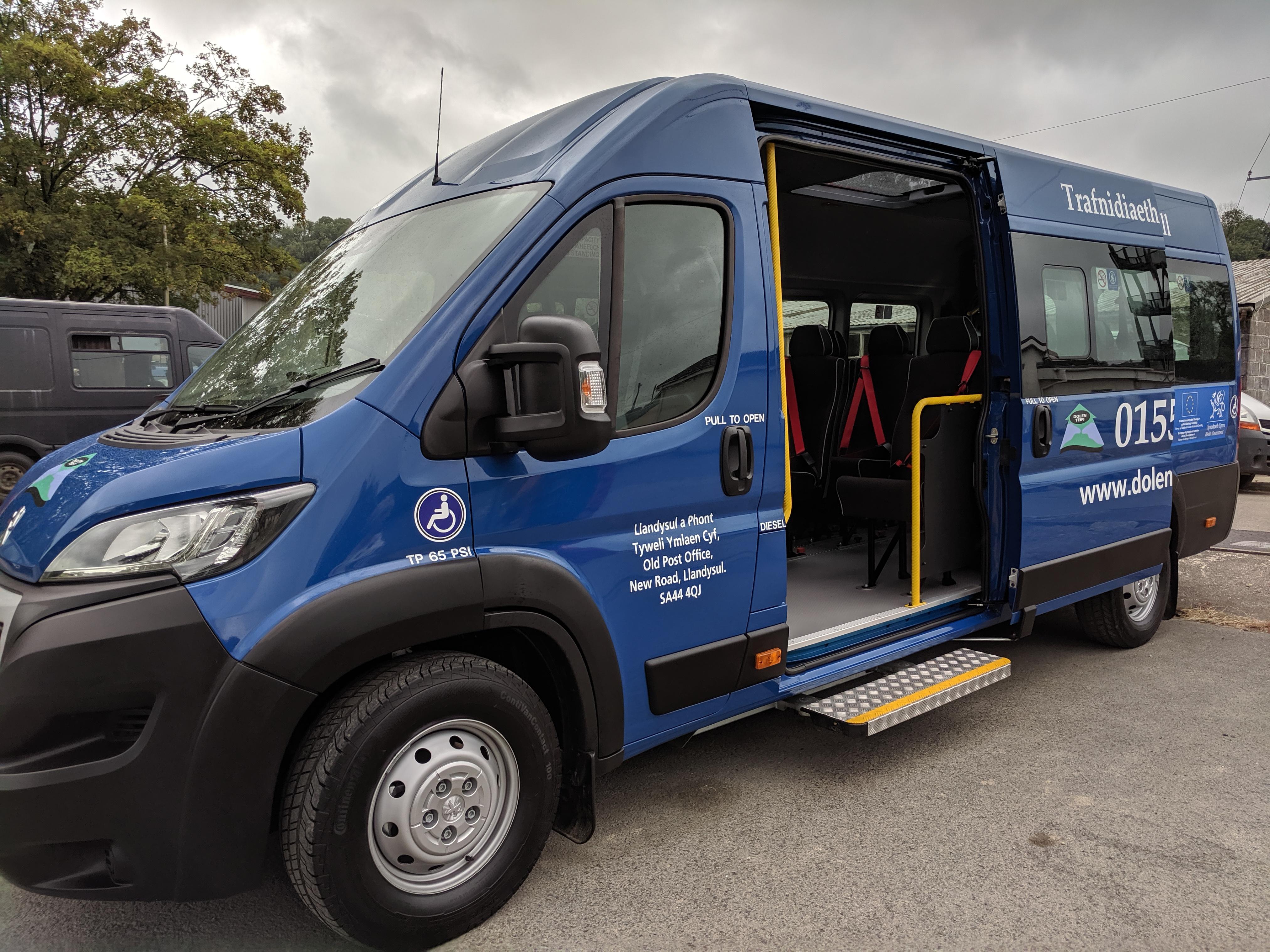 Side view of blue minibus, with door open.